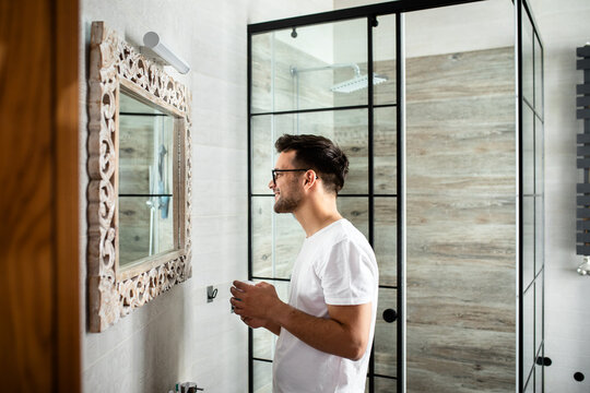 Young man going through morning routine in the bathroom applying face cream.
