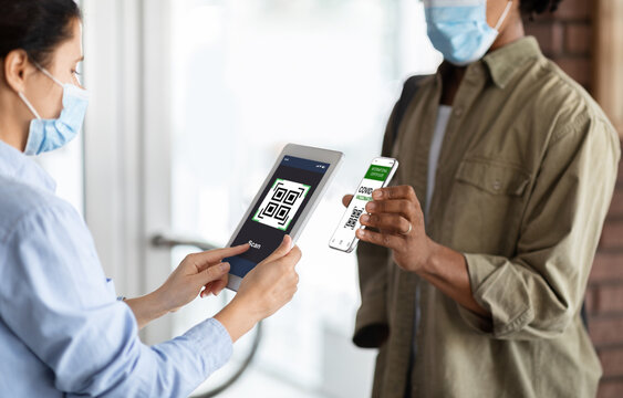 Female Worker With Digital Tablet Scanning Health QR Code Of Male Visitor