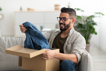 Satisfied Arab male client taking out new clothes from cardboard box, happy with delivery service at home