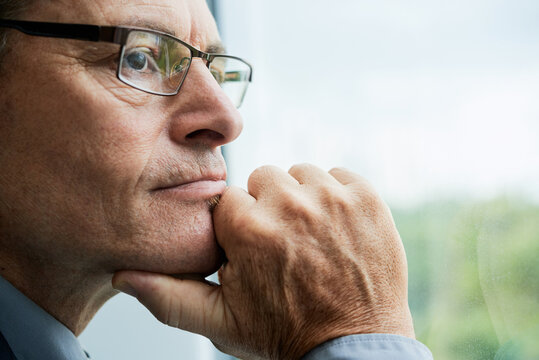 Headshot of thoughtful mature Caucasian man in glasses touching chin and contemplating cityscape through window