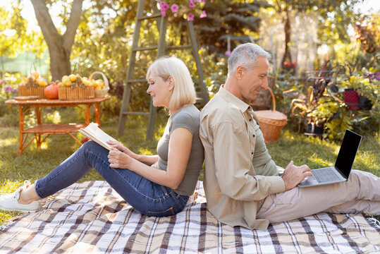 Retired married couple resting in garden, woman reading book while man using laptop, sitting back to back, side view