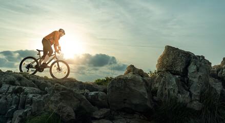 Obraz Mountainbiker fährt in den Bergen - fototapety do salonu