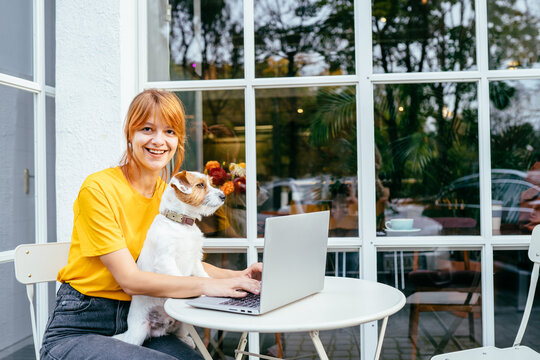 Adult tired upset woman work at cafe outdoor with dog remote workers and smart working day professional job typing on computer laptop, online modern people work writing on notebook and think