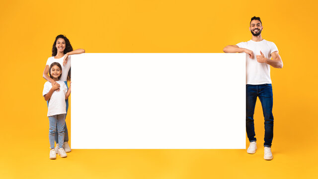Middle-Eastern Family Standing Near Big Empty Poster On Yellow Background
