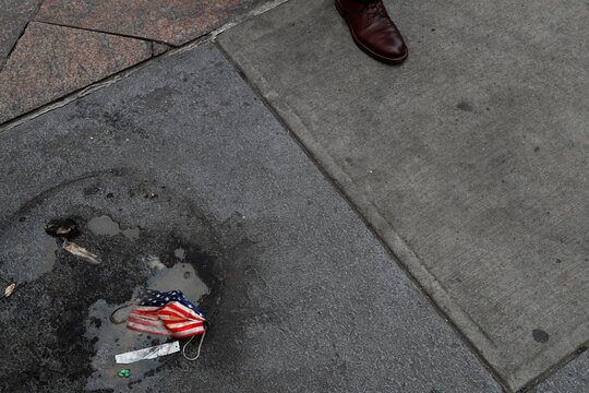 A protective face mask imprinted with the U.S. flag lays on the ground, amid the coronavirus disease (COVID-19) pandemic, as a person walks in New York City