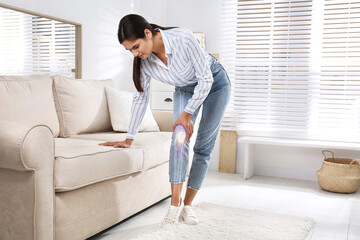 Fototapeta Sick young woman at home. Digital compositing with illustration of knee joint obraz