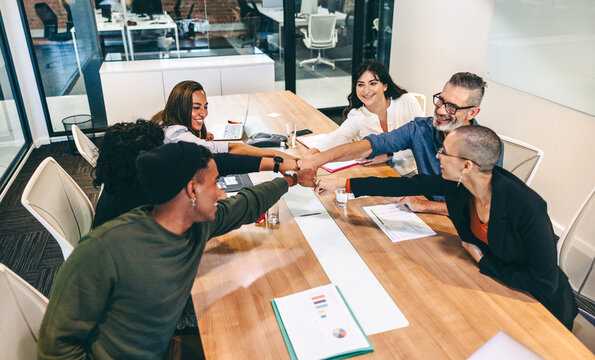 Group of cheerful businesspeople bringing their fists together in a boardroom