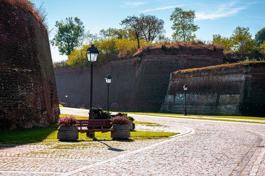 alba-iulia, romania - OCT 13, 2019: inner streets of alba carolina citadel in autumn. lanterns and benches by the walkway. huge walls around the path. popular travel destination