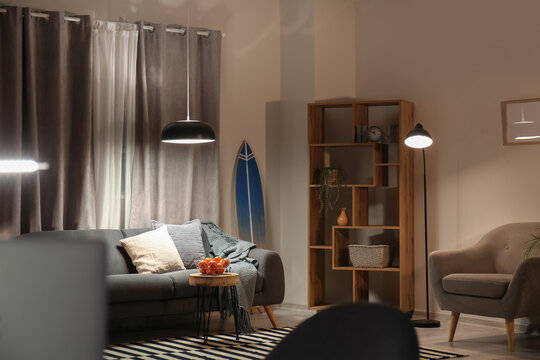Interior of modern stylish room with surfboard and sofa at night