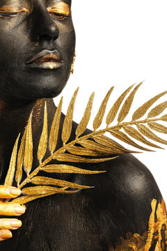 Beautiful young woman with  black and golden paint on her body and tropical leaf against white background