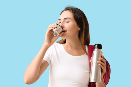 Female tourist with thermos on color background