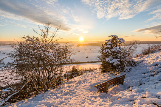 Scenic colourful sunset over beautiful winter landscape in the Swabian Alps with trees and bench in the foreground