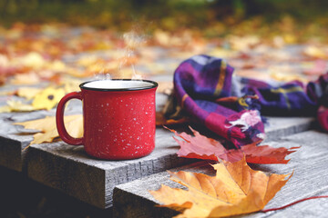 Obraz Autumn coffee or tea in a cup on a wooden table against the background of yellow fallen leaves and October weather. Autumn drink, mood and comfort concept. - fototapety do salonu