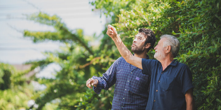 Handsome senior father with young son standing in backyard talking and laughing while looking and pointing up towards the sky during day