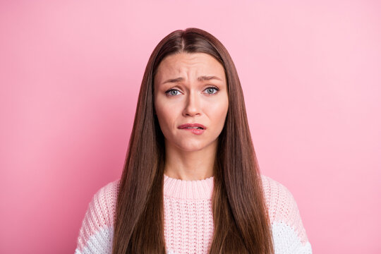 Photo portrait of guilty sad woman biting lip nervous unhappy isolated on pastel pink color background