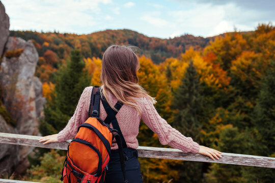 Woman traveler with backpack stands by rocks in Tustan in autumn Carpathian mountains. Tourism in Ukraine