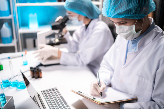 Medical healthcare researcher and scientist writing experiment detail on paper in clipboard while looking at laptop for details with colleague looking through microscope in background in laboratory