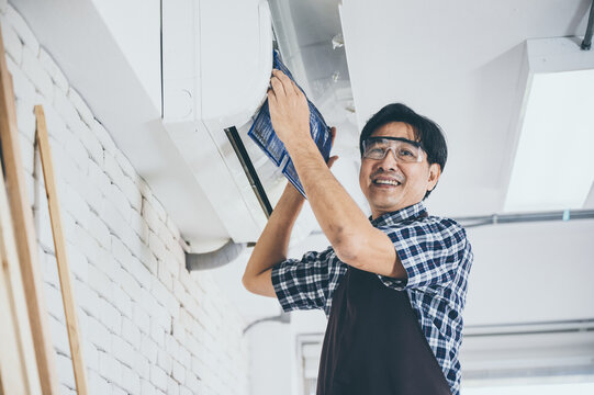 Young Asian male technician wearing safety glasses and apron cleaning air conditioner by removing the filter and fixing it back for further use