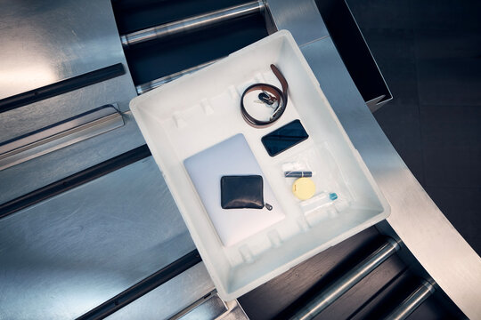 Personal Items, liquids, and laptop in container at airport security check before flight..