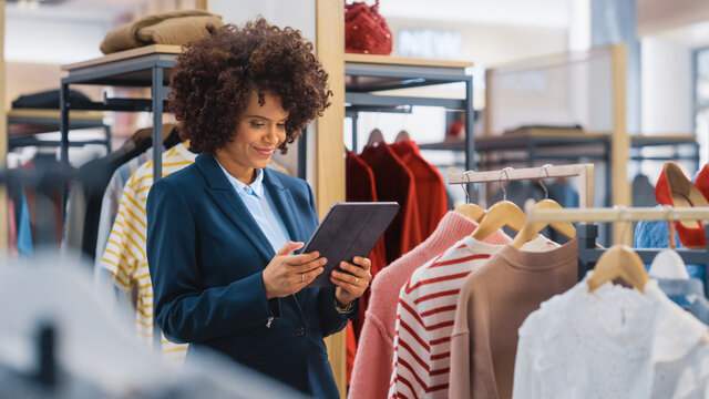 Clothing Store: Female Merchandising Manager Uses Tablet Computer To Create Stylish Fashion Collection. Professional Shop Sales Retail Assistant Checks Stock. Small Business Owner Orders Mall Items.