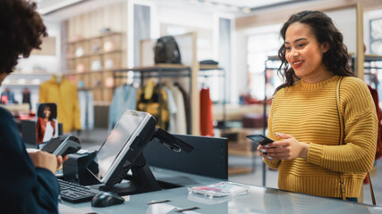 Obraz Clothing Store Checkout Cashier Counter: Woman Retail Sales Manager Accept NFC Smartphone and Credit Card Payments from a Young Female Customers for Clothes. - fototapety do salonu
