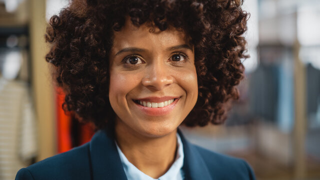 Portrait of a Happy Black Female with Stylish Afro Hair Smiling and Posing for Camera at Clothing Store. Small Business Owner in a Role of a Diverse Businesswoman or Sales Manager.