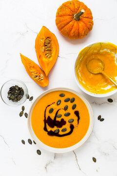 Homemade pumpkin soup with pumpkin oil and seeds