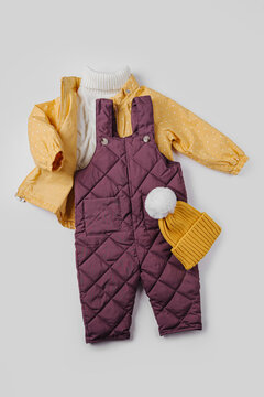 Yellow  jacket, warm pants and hat on white background. Set of baby clothes for winter. Fashion kids outfit..