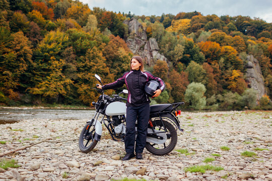 Woman biker travel by motorbike in fall. Motorcyclist enjoys autumn landscape in mountains having rest by forest