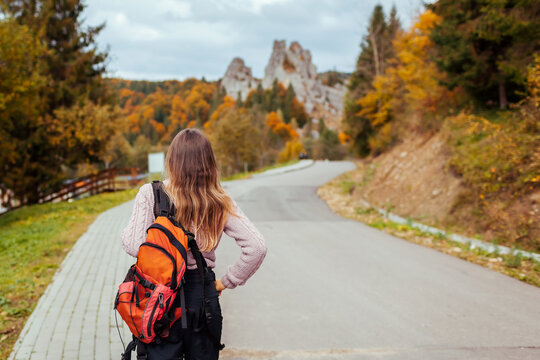 Woman traveler with backpack walking to rocks in Tustan in autumn Carpathian mountains. Tourism in Ukraine