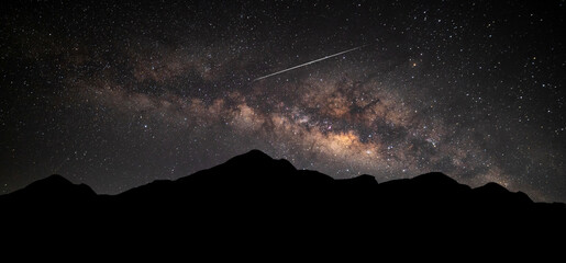 Panorama Milky Way. Night sky with stars and shooting stars with silhouette of dark the mountain. Space background
