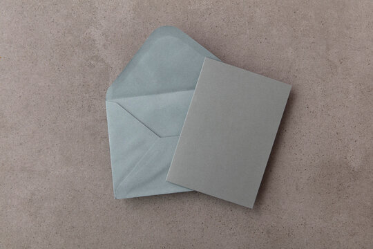Blank grey card with grey paper envelope template mock up on a concrete background