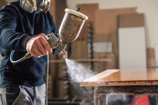 Process of varnishing or spraying wood by automatical spray in the professional joinery shop, industrial concept
