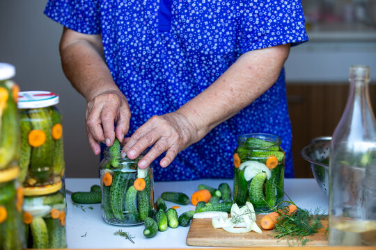 Process of homemade canning fresh, bio cucumbers to a jars by senior woman, food concept