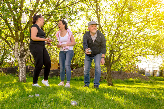 Glad, positive smiling family playing French traditional game petanque in the garden outside during lovely summer day, enjoying leisure time