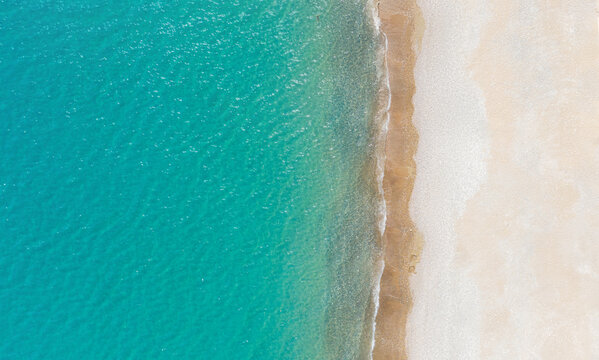 Empty white sand beach and calm turquise sea. Aerial view directly above, background with copy space