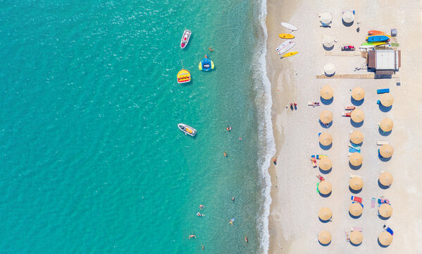 Sand beach with sunbeds, sunshades and water sports equipment, people swimming and taking sunbath. Aerial panorama directly above