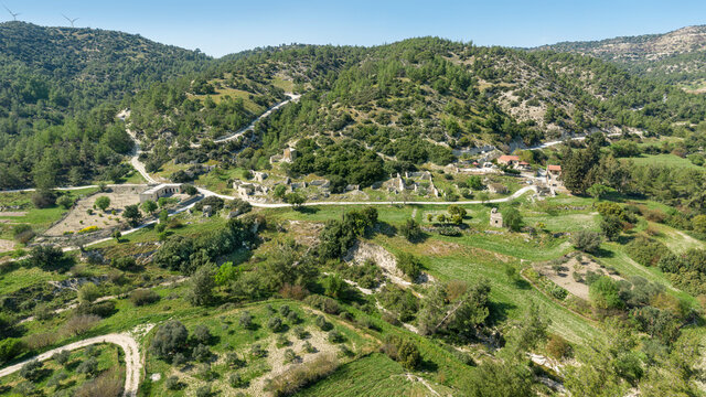 Rural  depopulation in Cyprus. Semi-abandoned village of Kato Archimandrita on a hill slope with old ruins and renovated houses, olive and carob trees gardens