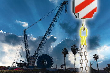A huge crane with a steel hook against the backdrop of palms and clouds.