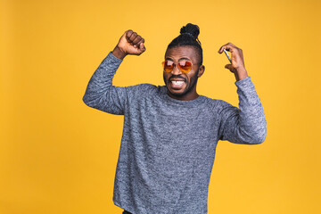 Fototapeta Photo of overjoyed black african american man knowing that he became winner of something so rejoicing enjoying news information while isolated over yellow background. obraz