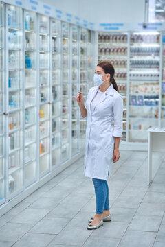 Woman pharmacist examining medicines on shelves
