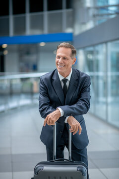 Cheerful man leaning on suitcase at airport