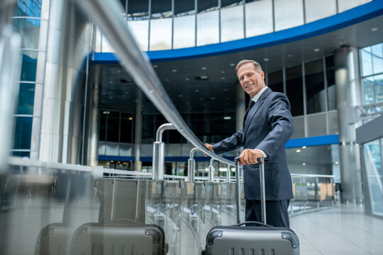Smiling business man with suitcase at airport