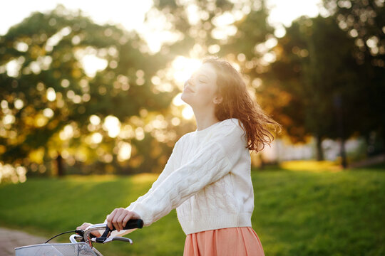 Young girl with a bike in a park in the morning