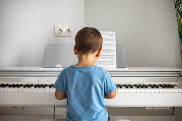 Cute baby boy playing white electrical forte piano pressing keys kid studying at musical school