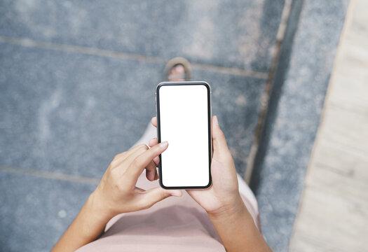 woman hand using phone white blank screen walking on path way