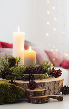 Composition of candles on  white table against the background of sofa at home