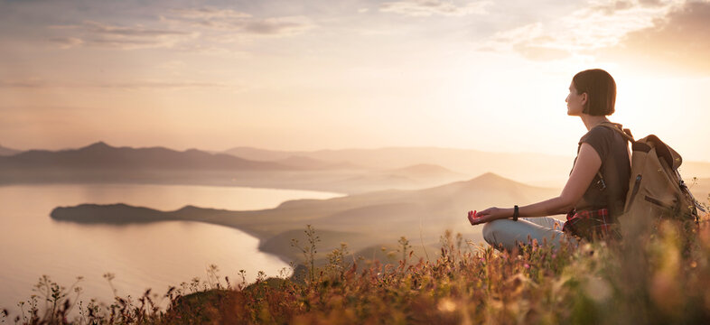 A young Asian woman with backpack Sitting on hill slope and enjoying the view of the sunset sea