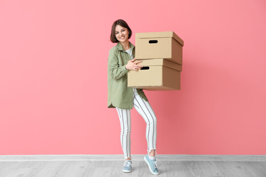 Young woman with wardrobe boxes near color wall