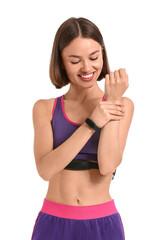 Fototapeta Sporty female runner checking pulse on white background obraz